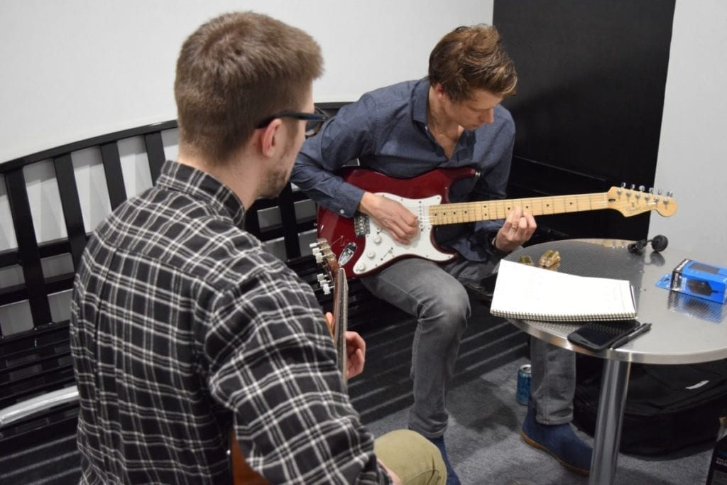 doug and an adult student focusing on his electric guitar lesson at home