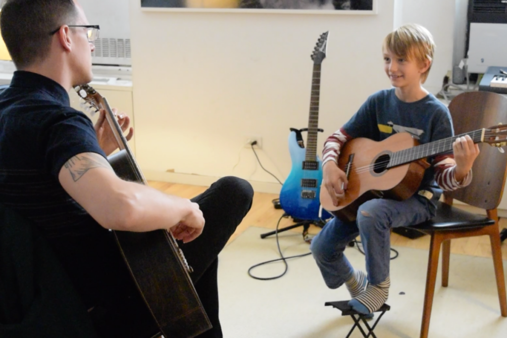 young student with classical guitar smiling in sunlight with teacher