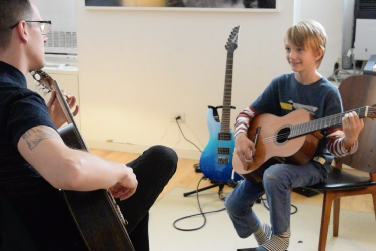 Rob and a child student playing guitar and smiling in the sunlight coming through the window