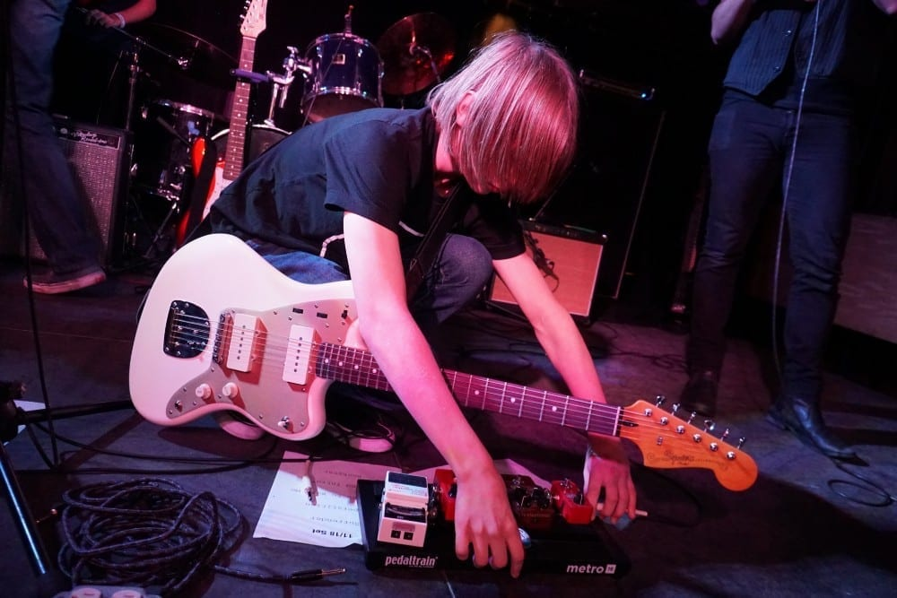 teen rock band shredder checking his pedals